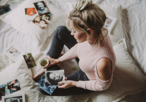Woman, bed, sit, photos, view, cup, hold,
