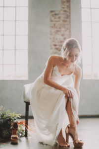 Bride, sitting, puts on her shoes,