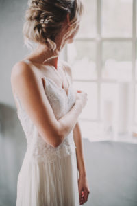Bride is standing at the window, side view,