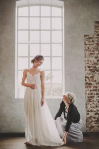 Bride trying on her dress, dressmaker