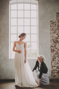 Bride trying on her dress, dressmaker