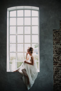 Bride sits thoughtful on windowsill,