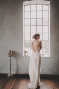 Bride is standing at the window, back view,