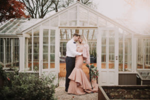 Bridal couple standing in garden, hug,