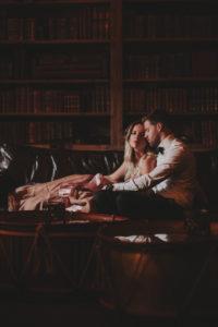 Junges Paar sitzt verliebt auf dem Sofa in einer Bibliothek,
