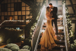 Bridal couple stand on a staircase and kiss each other