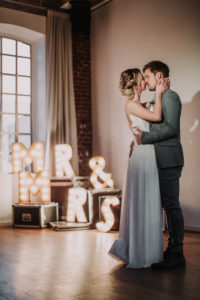 Happy bridal couple, closed eyes, standing, hug, decoration, illuminated letters,