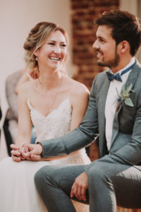 Bridal couple, sitting, holding hands, smiling,