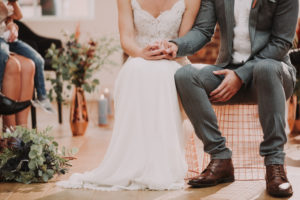 Bridal couple, sitting, holding hands, detail,