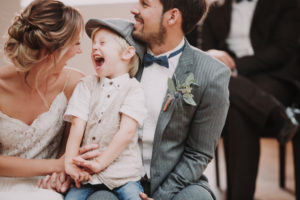 Bridal couple and boy, sitting, having fun,