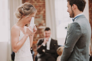 Bride and groom, standing, bridal vow, reading, reading, laughing,