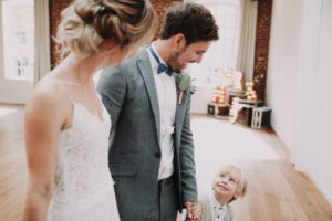 Bridal couple and boy holding hands, happy,