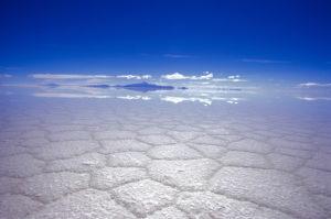 Bolivien, Salar de Uyuni, Salzwüste,  Horizont, Gebirge, Spiegelung  Südamerika, Altiplano, Landschaft, Wüste, Salztonebene, Salzsee, Trockenheit, Risse, Natur, Weite, Ferne, menschenleer, lebensfeindlich,  blau, weiß
