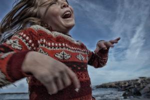 Little girl running on a rocky beach