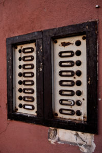 Damaged door bell nameplate at a wall of a house