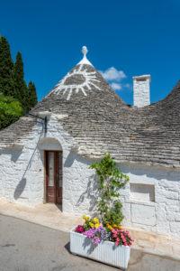 Alberobello, Provinz Bari, Salento, Apulien, Italien, Europa. Die typischen Trulli Häuser mit ihrem kegelfärmigen Dach und den Symbolen