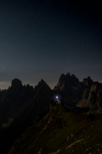 Monte Campedelle, Misurina, Auronzo di Cadore, Province of Belluno, Veneto, Italy, Europe. A mountaineer admires the starry sky over the Cadini group