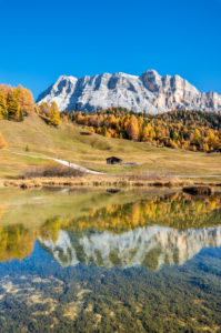 Hochabtei / Alta Badia, Bolzano province, South Tyrol, Italy, Europe. Autumn in the Armentara meadows. The peaks of the Zehnerspitze and the Heiligkreuzkofel are reflected in a small mountain lake