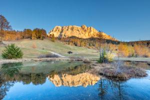 Hochabtei / Alta Badia, Provinz Bozen, Südtirol, Italien, Europa. Sonnenuntergang über den Armentarawiesen. In einem kleinen Bergsee spiegeln sich die Gipfel der Zehnerspitze und des Heiligkreuzkofel