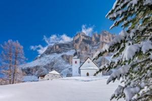 Hochabtei / Alta Badia, Provinz Bozen, Südtirol, Italien, Europa. Die Schutzhütte Heilig Kreuz Hospiz und die Wallfahrtskirche von Heilig Kreuz unter den Felswänden des mächtigen Heiligkreuzkofel