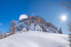 Hochabtei / Alta Badia, Bolzano province, South Tyrol, Italy, Europe. The shelter Heilig Kreuz Hospiz and the pilgrimage church of Heilig Kreuz under the cliffs of the mighty Heiligkreuzkofel