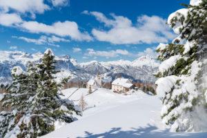 Hochabtei / Alta Badia, Provinz Bozen, Südtirol, Italien, Europa. Die Schutzhütte Heilig Kreuz Hospiz und die Wallfahrtskirche von Heilig Kreuz. Im Hintergund die Puezgruppe, die Geislerspitzen und der Peitlerkofel