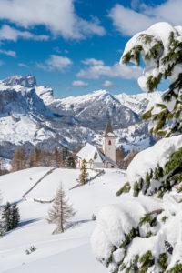 Hochabtei / Alta Badia, Provinz Bozen, Südtirol, Italien, Europa. Die Wallfahrtskirche von Heilig Kreuz. Im Hintergund die Puezgruppe und die Geislerspitzen