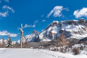 Hochabtei / Alta Badia, Provinz Bozen, Südtirol, Italien, Europa. Kruzifix auf den Armentarawiesen. Im Hintergrund die Neunerspitze