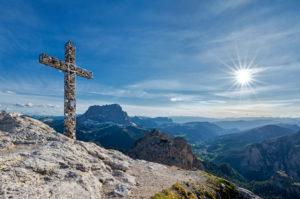 Grödner Joch, Provinz Bozen, Südtirol, Italien. Das Gipfelkreuz der Großen Cirspitze. Im Hintergrund der Langkofel und das Grödner Tal