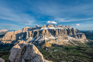 Gardena Pass, Bolzano Province, South Tyrol, Italy. A mountaineer at the summit of the Großer Cirspitze admires the mountain panorama of the Dolomites