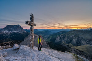 Gardena Pass, Bolzano Province, South Tyrol, Italy. A mountaineer at the summit of the Große Cirspitze admires the sunset