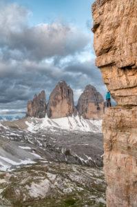 Drei Zinnen, Dolomiten, Provinz Bozen, Südtirol, Italien. Ein Bergsteiger bewundert das Bergpanorama auf einem ausgesetzten Felsband