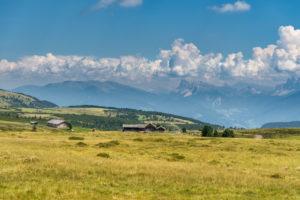 Villanders, Provinz Bozen, Südtirol, Italien. Almhütten auf der Villanderer Alm mit Blick zu den Dolomiten mit Peitlerkofel und Geislerspitzen