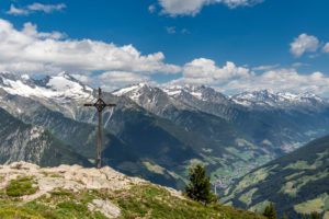 Sand in Taufers, Bolzano Province, South Tyrol, Italy. The summit cross on the Kleiner Nock in the Speikboden hiking area. In the background the Ahrntal with the Zillertal Alps