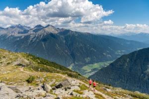 Sand in Taufers, Provinz Bozen, Südtirol, Italien. Wanderer auf dem Panoramaweg im Wandergebiet Speikboden mit Tiefblick in das Tauferer Tal