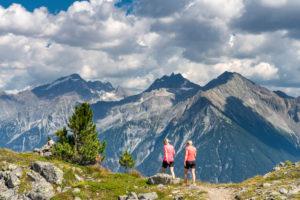 Sand in Taufers, Provinz Bozen, Südtirol, Italien. Wanderer auf dem Panoramaweg im Wandergebiet Speikboden mit Blick zur Rieserfernergruppe mit den Gipfeln Schneebiger Nock, Fensterleekofel und Windschar.