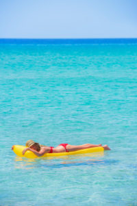 Woman relaxing on inflatable mattress,  Formentera, Balearic Islands, Spain