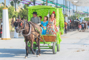 People wearing traditional dresses riding on a carriage, Malaga Festival, Malaga, Andalusia, Spain,