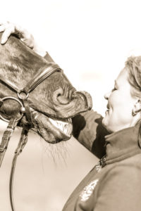 young woman stroking head of a horse