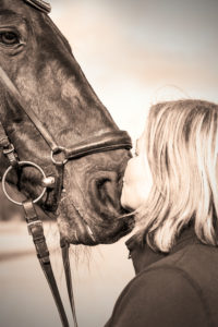 young woman is kissing horse
