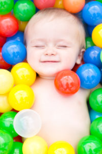Baby lies naked in the ball bath, portrait