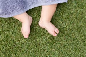 Baby in Wiese liegend, Füße Detail