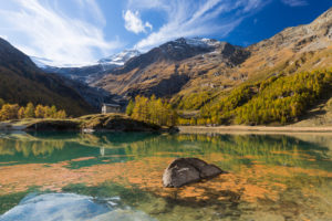 The afternoon sun bathes the area around the reservoir Lago Palü on the Alp Grüm near Poschiavo in an autumnal light, canton Grisons, Switzerland,