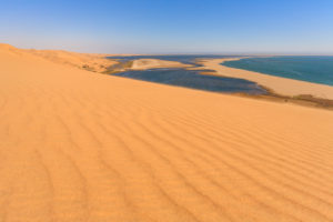 Sand dunes modeled by wind meet the Atlantic Ocean and lagoons in Walvis Bay Namib Desert Erongo Region Namibia Southern Africa
