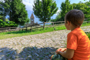Child on footpath admires the Abbey of San Pietro in Vallate Piagno Sondrio province Lower Valtellina Lombardy Italy Europe