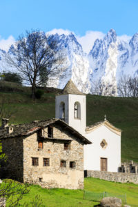 Alpine church and green meadows framed by the snowy peaks in spring Daloo Chiavenna Valley Valtellina Lombardy Italy Europe