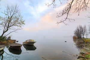 Boats moored framed by mist of autumn at dawn Pozzo di Riva Novate Mezzola Chiavenna Valley Lombardy Italy Europe