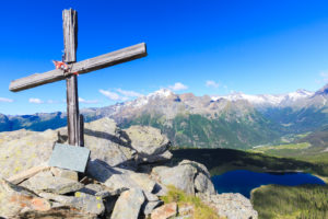 Wood cross above Lake Palô framed by Mount Disgrazia seen from Monte Roggione Malenco Valley Valtellina Lombardy Italy Europe