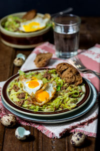 Pan dish, pointed cabbage, minced beef, fried egg from quail eggs