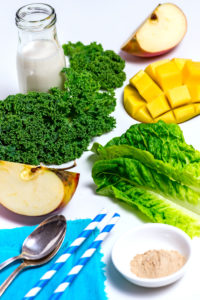 All ingredients spread out on a white background, milk bottle, kale, mango hedgehog, apple quarters, Romaine lettuce, two straws, two silver spoons, nutritional supplements in a white bowl